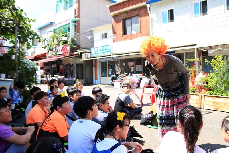 구_로컬 아트트래킹 신나는 예술여행, 구_로컬 아트트래킹에 참여한 온수초등학교 어린이들이 시장 공터에서 펼쳐지는 연극 '희희희 미용원'을 관람하고 있다.