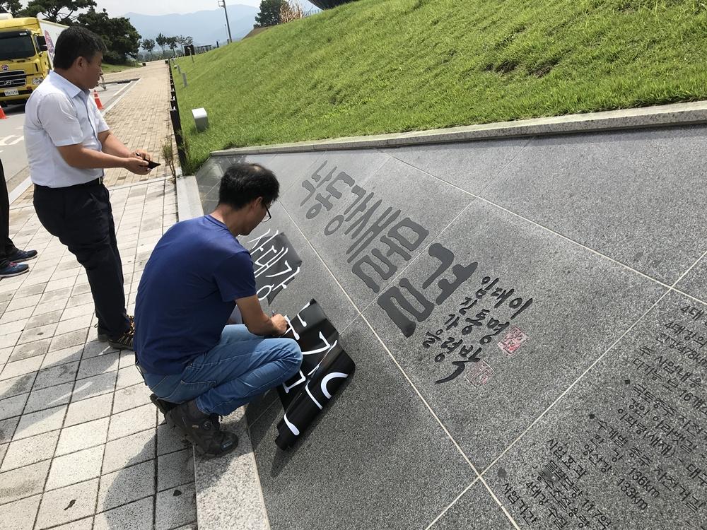 """낙동강 새물결이라는 이명박 전 대통령의 휘호가 새개져 있는 기념석에 대구 작가들이 """"죽어가는 4대강 눈감은 미술제 반대한다""""는 문구가 박힌 시트지를 붙이고 있다"""