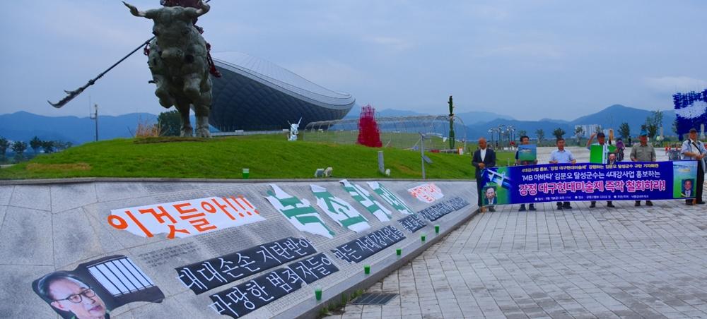 """""""이것들아 녹조라떼 어쩔거냐?""""라는 문구를 붙인 4대강 기념비 앞에서 강정 대구현대미술제 반대 집회를 벌이고 있다."""