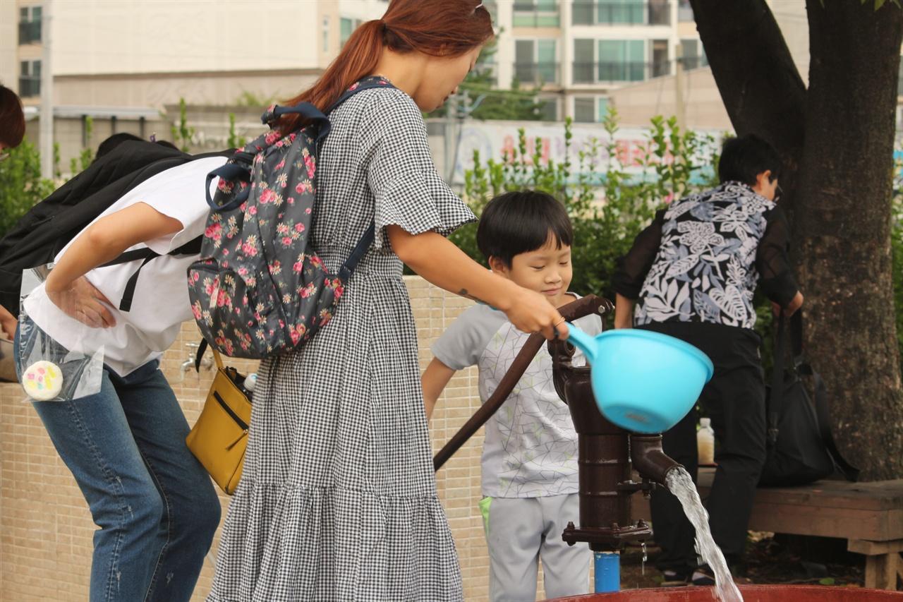부모와 함께 수동펌프 체험을 하고 있는 모습 한 어린 아이가 물을 이용해 지하수를 이용하던 펌프(수도)를 체험해 보고 있다.