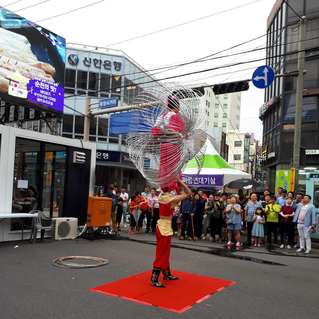 아크로스 공연 순천푸드아트페스티벌에서 마련된 공연으로, 중국 아크로스 남녀 한 쌍이  훌라후프 기예를 선보이고 있다. 그 옆에 있는 흰색 건물이 방문객 쉼터로 마련된 G테이너이다.