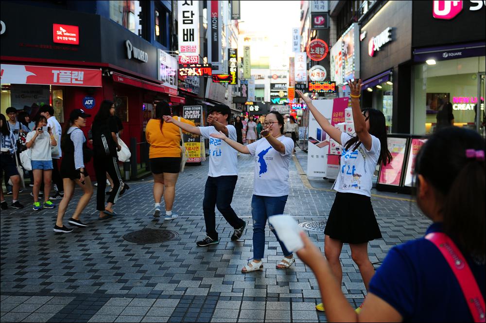 대전청년회 회원들이 통일 노래에 맞춰 몸짓을 하자 지나가는 사람들이 발길을 멈추거나 눈길을 보내고 있다.