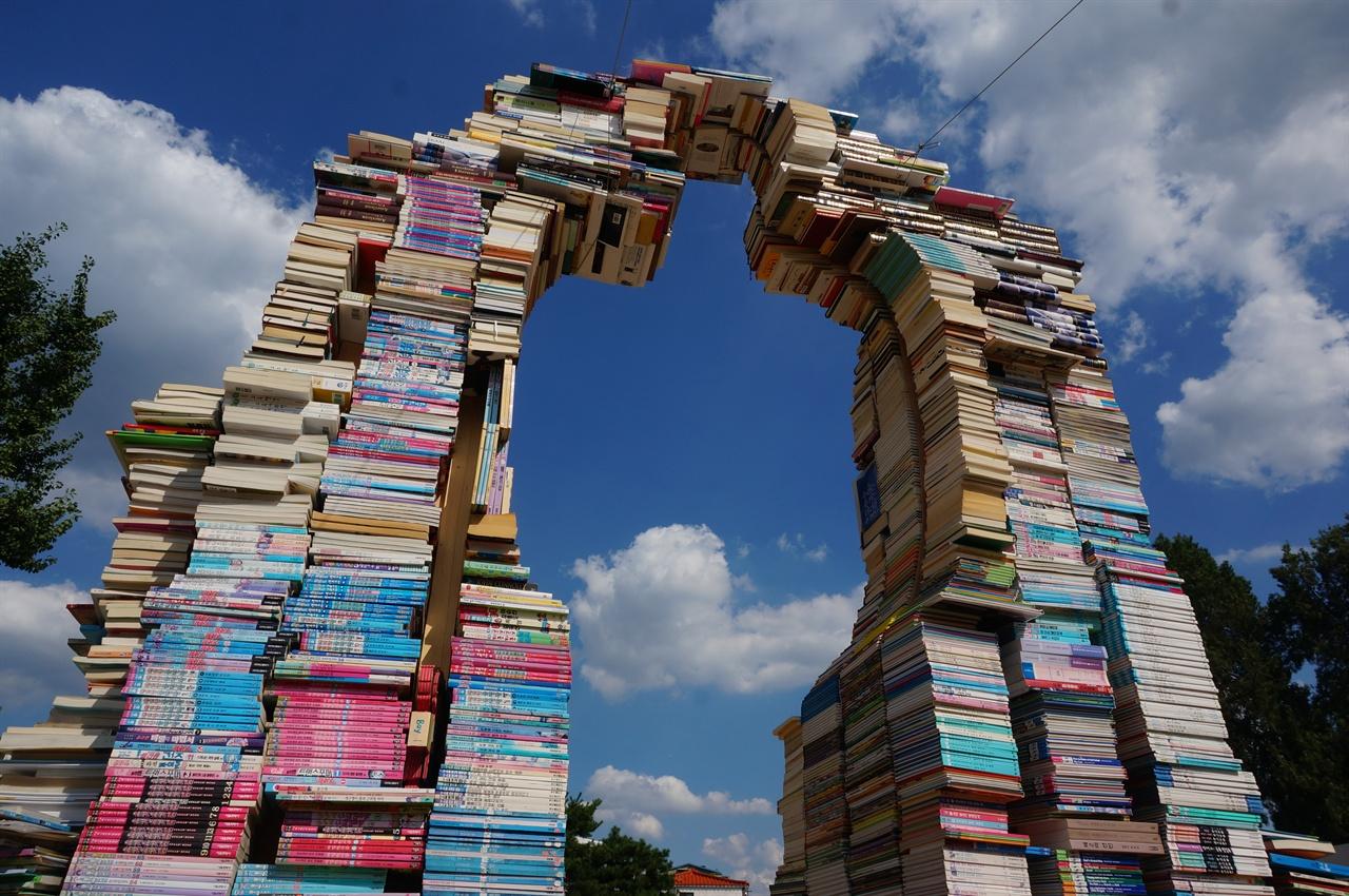 조은하 작가의 <책의 기원>. 책을 켜켜이 쌓아 만든 사람 조형물, 책은 물리적인 형태를 넘어 인간으로부터 기원한다는 의미를 담고 있다. 수원 행궁광장 및 행궁동 일대에서 열리고 있는 2018 수원한국지역도서전에서.