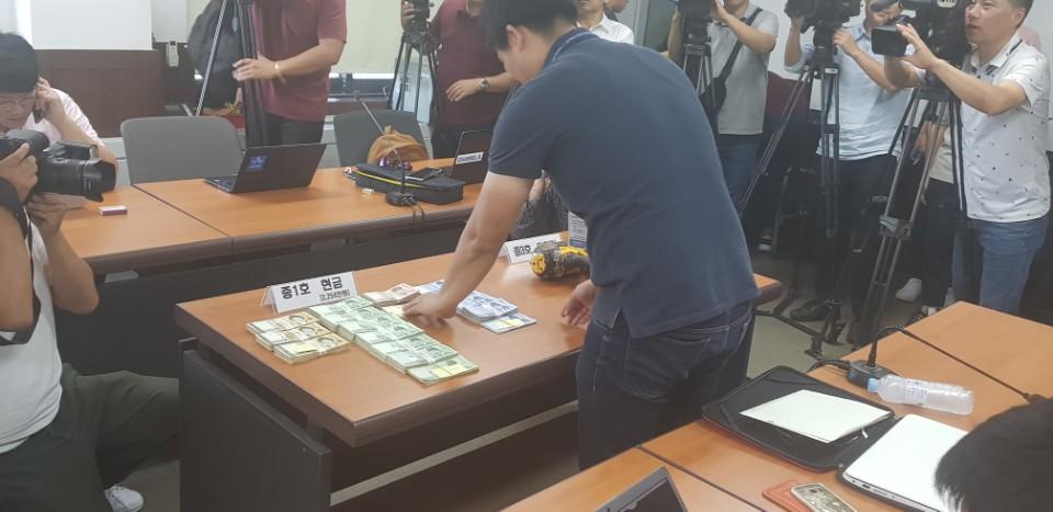 증거물을 정리하고 있는 경찰 당진 경찰서 직원들이 증거물인 현금과 타정기를 정리하고 있다.