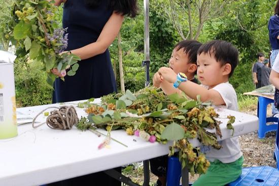 박주녀씨가 수확한 넝쿨로 장민준 군이 리스를 만들고 있다.