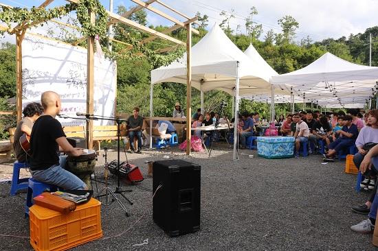축제 참가자들이 솔티맥주를 마시며 공연을 즐기고 있다.