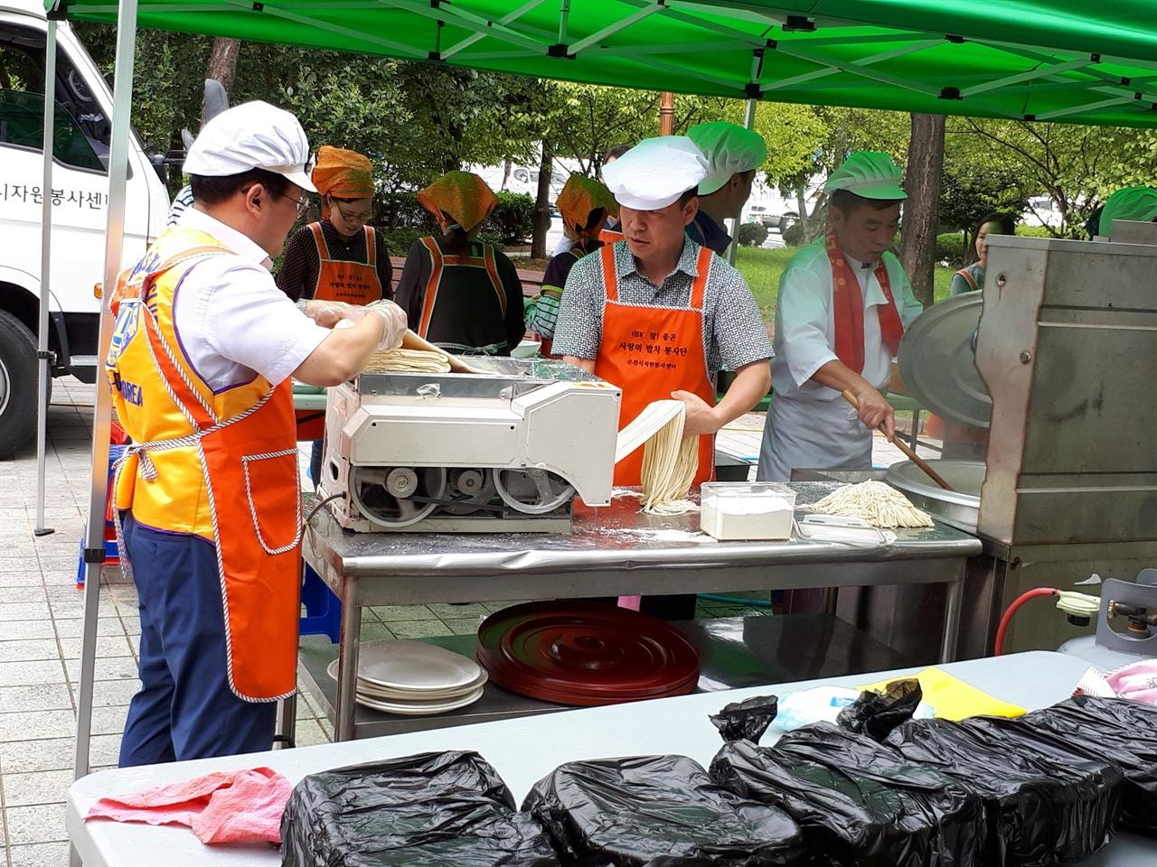 식사를 준비하는 봉사자들 9월 11일 메뉴는 짜장면이었다. 봉사자들이 즉석에서 바로 제면기에서 면을 뽑아 삶아 짜장 소스를 올려 만들었다. 그리고 배식 담당 봉사자들이 방문객들이 앉은 곳에 직접 배달해 주었다.