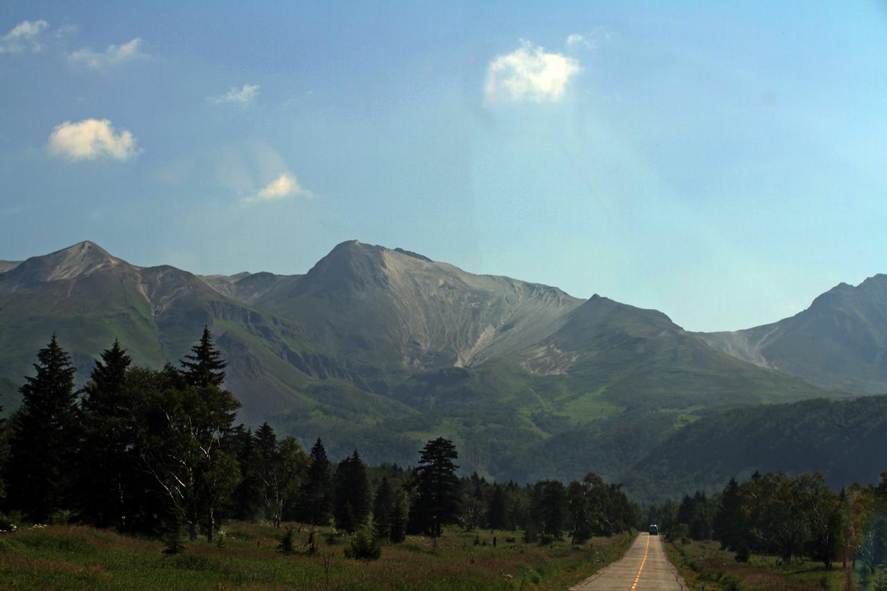 백두산 오르는 길  산문을 통과하여 백두산 서파로 오르는 길. 매표소를 지나 셔틀버스를 타고 대략 1시간 정도를 이동하면 천지로 향하는 계단 입구에 이르게 된다. 가운데 보이는 산이 백두산 천지가 있는 정상이다.