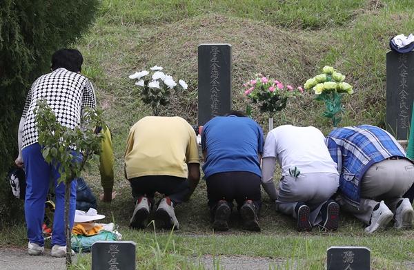 추석 연휴가 2주 앞으로 다가온 9일 부산 금정구 영락공원에서 성묘객들이 조상묘에 벌초를 하고나서 절 하고 있다.