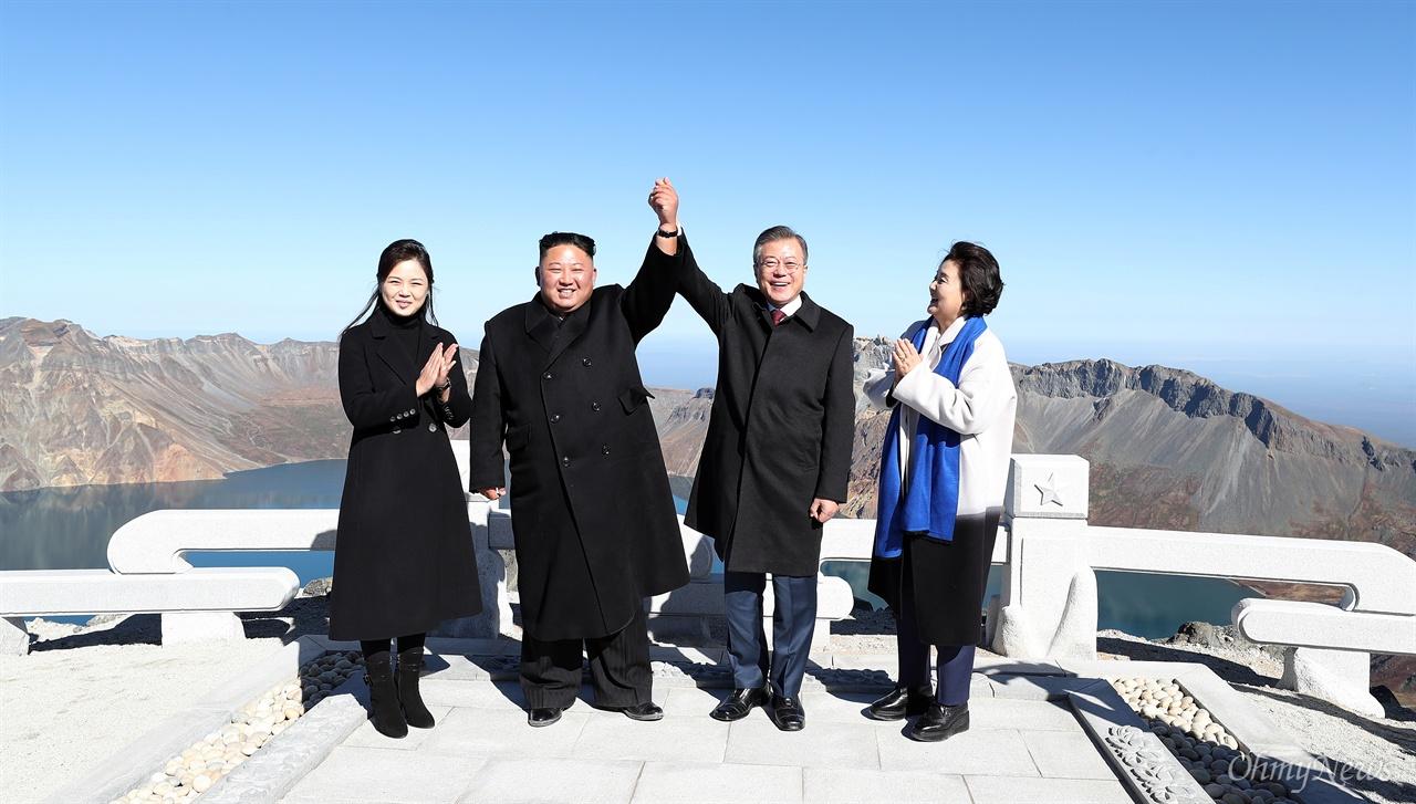 백두산 전설 하나 추가! 평양정상회담 사흘째인 20일 오전 문재인 대통령과 김정은 국무위원장이 백두산 정상인 장군봉에 올라 손아 잡아든 가운데, 김정숙 여사와 리설주 여사가 박수를 치고 있다.
