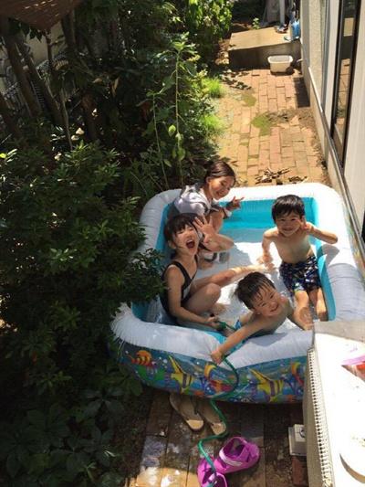 집 마당에서 간이수영장을 만들어 물놀이를 하는 아이들.