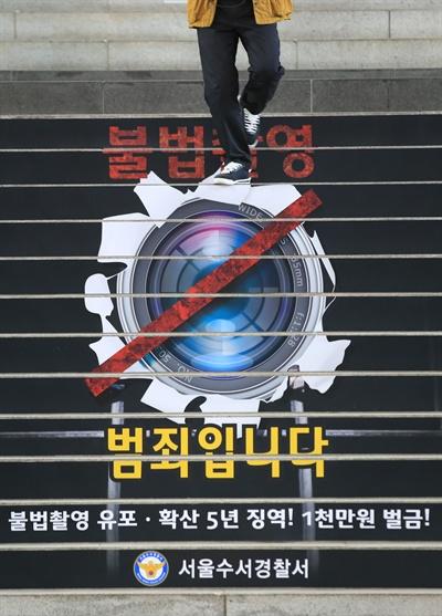'불법촬영은 범죄입니다' 지난 20일 오후 서울 수서역 계단에 불법촬영 근절 홍보물이 붙어있는 모습.