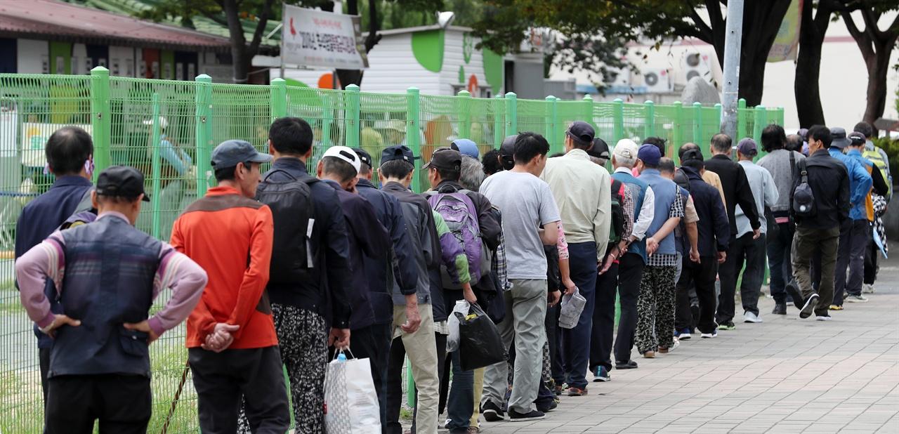 추석인 24일 오전 부산 동구 부산진역 무료급식소에서 점심을 먹기 위해 길게 줄을 선 사람들.