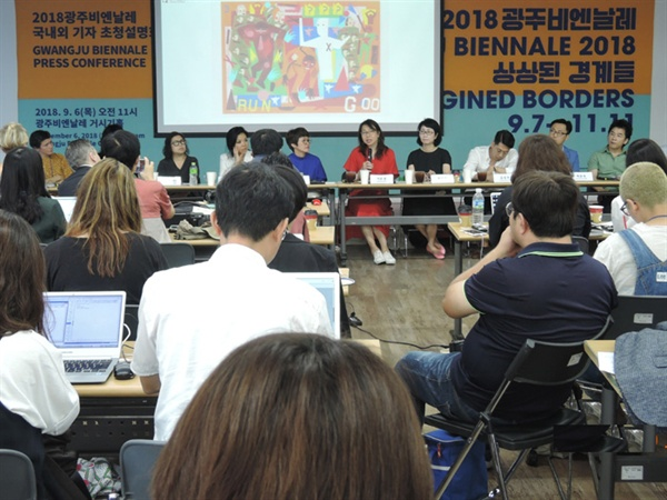 2018년 9월 6일 광주비엔날레 '거시기홀'에 열린 국내외기자회견에 참가한 11명의 큐레이터와 기자들 관계자들. 배경에는 아프리카계미국인을 대변하는 작가 '니나 샤넬 애브니'의 작품이 보인다
