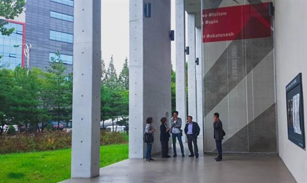 관리동 건물과 본관을 연결하고 있는 기둥들을 통해 완충과 산책의 경험을 제공한다. (김광수 건축가와 민주화운동기념사업회 임직원의 모습)