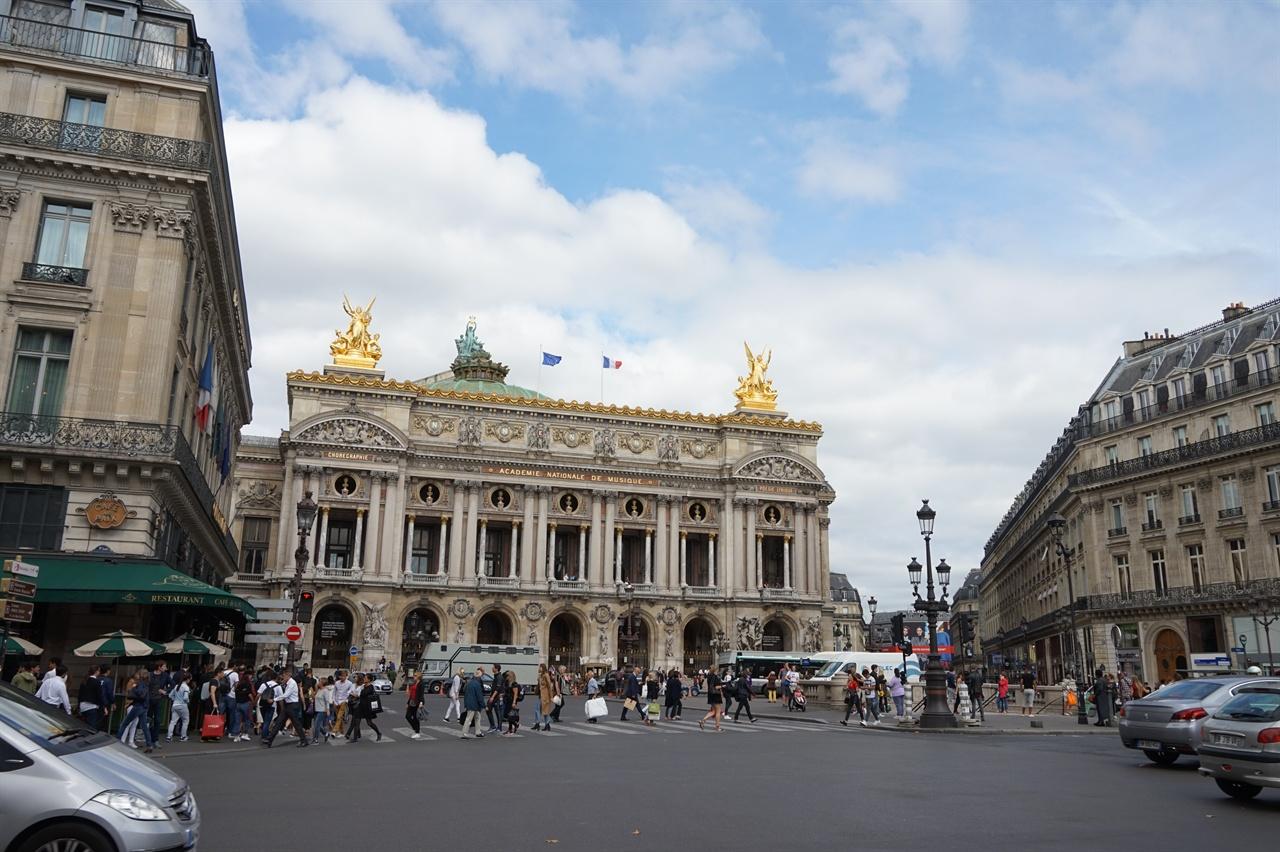 중앙의 오페라 가르니에 왼쪽 건물의 녹색 차양이 쳐진 자리가 카페 드라페다.