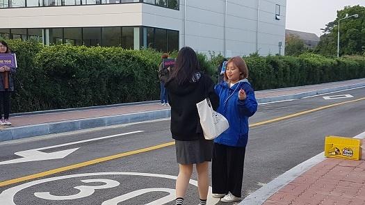 충남의 시민단체 회원이 논산 여상 학생에게 사탕을 나눠 주고 있다.