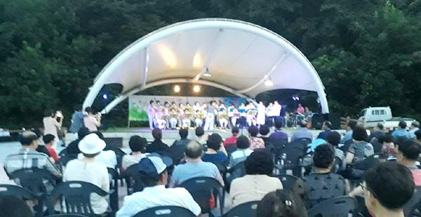 선선한 가을바람이 불어오는 만세음악회에서 주민들이 사이좋게 붙어앉아 구행모와 모란꽃하모니의 하모니카 연주를 듣고 있다.