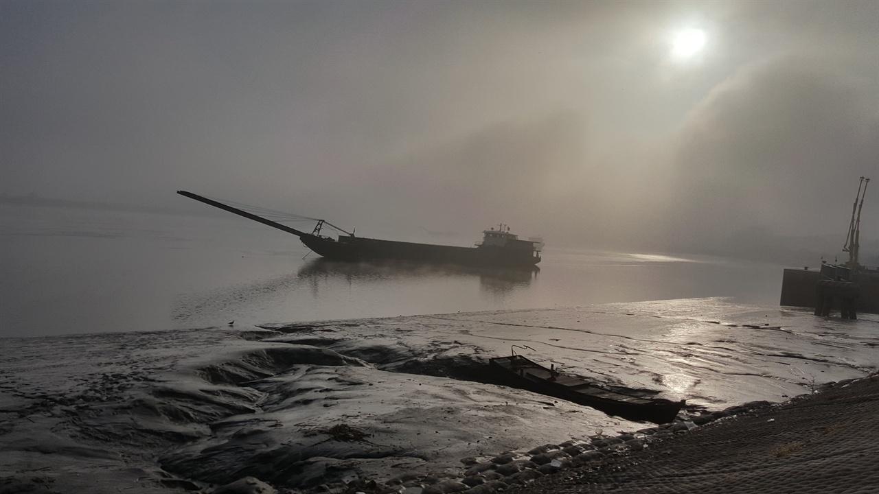 단둥시 압록강변에서 단둥시 압록강변에서 새벽 푸른 안개 속에 떠있는 배 한 척