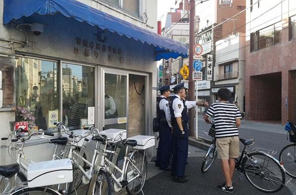 파출소 앞에서 외국인 관광객에게 길을 가르쳐주고 있는 일본 경찰관들.