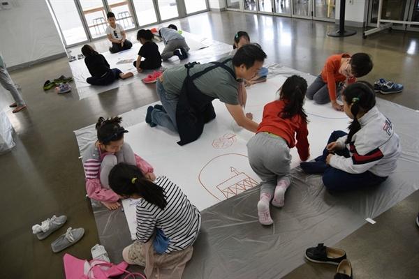 창의예술놀이터 '별별우리'에 참가한 아이들과 학부모가 함께 작품을 만들고 있다