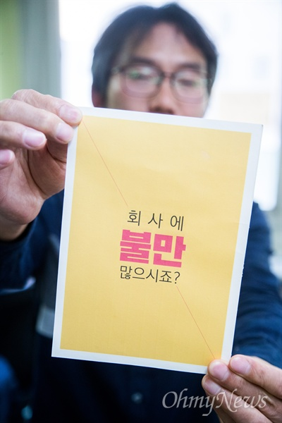 직장갑질119 박점규 위원이 포스터를 들고 있다.