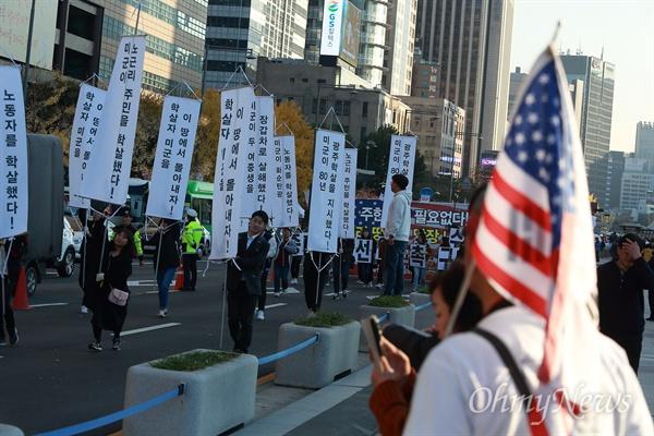 3일 오후 서울 광화문광장에서 '박대통령 무죄석방' 티셔츠를 입고 태극기와 성조기를 든 박근혜 지지자가 '11.3자주독립선언대회'에 참석한 국민주권연대 회원들의 행진을 지켜보고 있다.