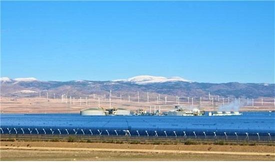 스페인 안달루시아 지방 그라나다시 외곽 과딕스 고원에 있는 안다솔 태양열 발전소. 낮에 모은 태양열에너지를 소금에 저장하는 회색 건물 2개가 가운데 둥그렇게 보이고 뒤편으로 멀리 풍력발전기들이 돌아가고 있다.