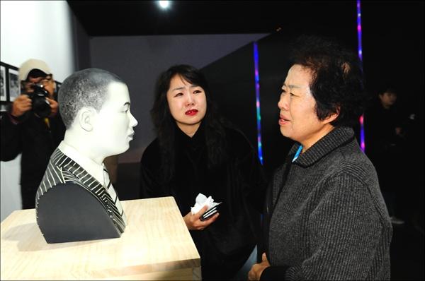 어버지의 3D프린팅 입체형상을 보고 눈물을 글썽이는 문양자 씨(오른쪽). 이를 지켜보는 정윤선 작가도 눈물을 글썽였다.