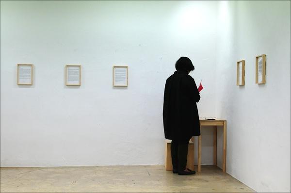 '콜렉트' 팀의 텍스트 전시물이 전시된 공간. 한 관람객이 모퉁이 책상 위에 전시된 기록물을 읽어 보고 있다.