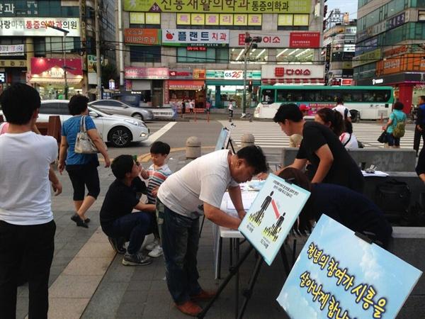 시흥청년아티스트가 주민청구방식으로 <시흥시 청년 기본 조례>제정 운동을 위해 길거리에서 서명을 받는 모습이다.