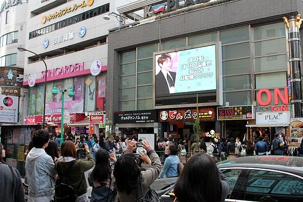 신오쿠보 거리 대형 스크린에 비친 샤이니 고 김종현의 모습을 일본 학생들이 열심히 찍고 있다.