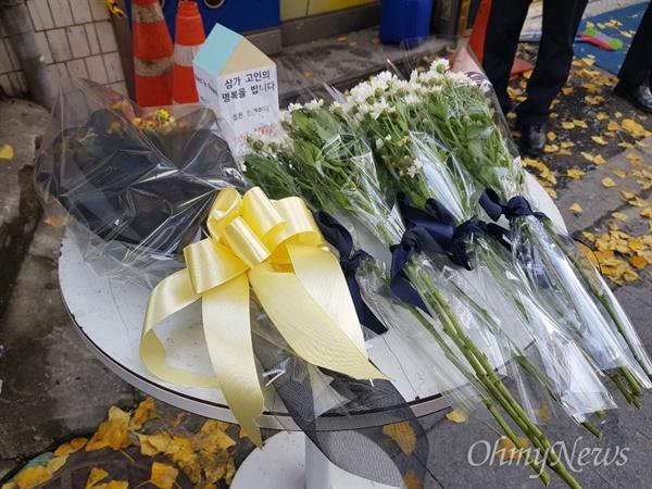 """9일 새벽 화재로 18명의 사상자가 발생한 서울 종로 관수동 고시원 앞에 희생자를 추모하는 꽃들이 놓여 있다. 이날 헌화한 윤성로 전국세입자협회 국장은 """"나도 10년 전에 두 달간 고시원에 살았는데 옆 방에서 자는 사람 코고는 소리까지 들리는 열악한 공간이었다""""면서 """"(오늘 희생자가) 내가 될 수도 있다는 생각에 찾아오게 됐다""""고 밝혔다."""