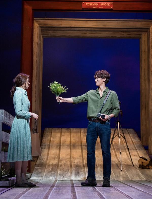 로즈먼 다리에서 로버트가 프란체스카에게 꽃을 선물하고 있다.