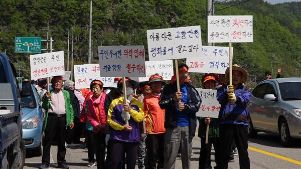 경북 영덕군 주민들이 '풍력단지 중단할 때까지 결사항전' 등의 구호가 적힌 손팻말을 들고 마을 도로를 행진하고 있다.