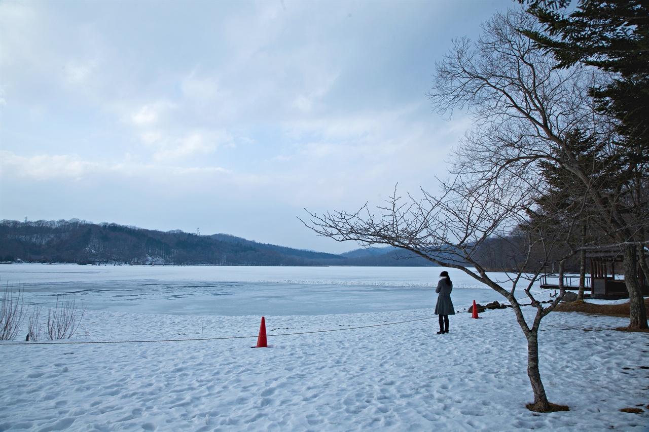 얼어붙은 홋카이도의 호수를 바라보는 여행자. 시적인 풍경이다.