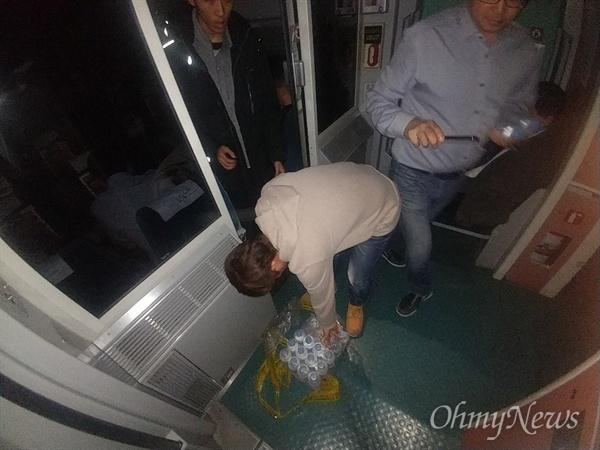 비상용 생수를 가져가는 승객 20일 오후 단전사고로 충북 청주 오송역에 멈춰선 KTX414 열차 안에서 승객들이 비상용 생수를 가져가고 있다. 전체 18호 개의 객차 중 18번 째 객차에 놓여있어, 멀리있는 승객들이 식수를 가져가는데 큰 불편을 겪었다.