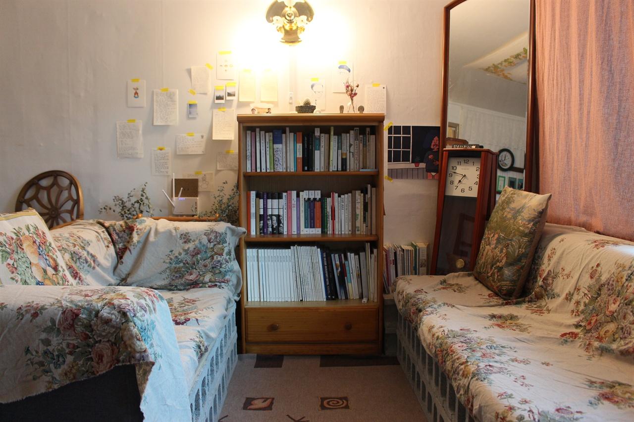깨끗한 천이 깔린 소파, 책장, 그리고 시계와 거울만으로 충분히 아늑하다.