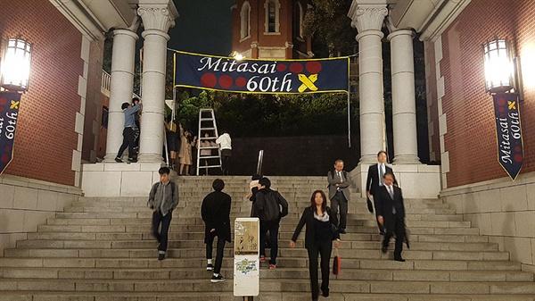 게이오대학 학생들이 학교 입구 건물에 축제 플래카드를 걸고 있다.