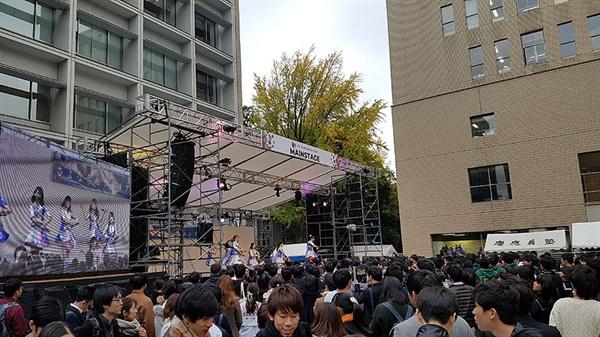 게이오대학 특설무대에서 인기 여자 아이돌 그룹이 노래를 부르고 있다.