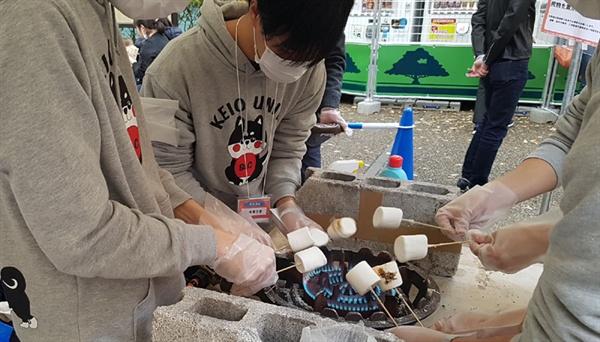 게이오대학 대학축제에서 먹거리천막에 참가한 학생들이 떡을 꼬치에 꿰어 굽고 있다.