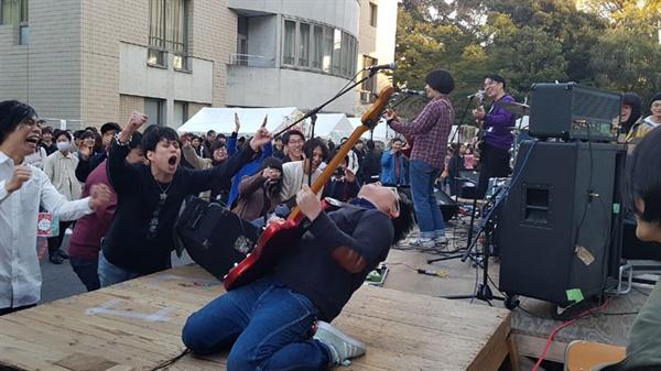 게이오대학 대학축제에서 스테이지에 오른 밴드의 열정적 공연에 학생들이 환호하고 있다.