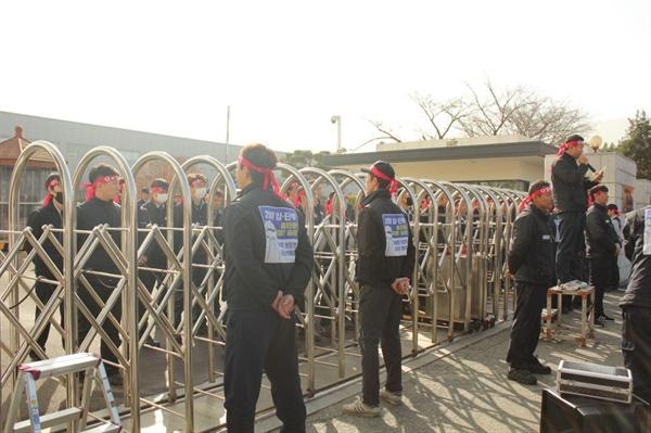 11월 28일 현대위아 창원2공장 정문이 봉쇄된 가운데 비정규직들이 안팎에 모여 있다.