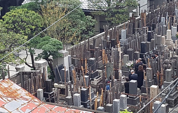 옥탑방에서 내려다본 건너편 사찰의 묘지. 한 가족이 참배하고 있다.