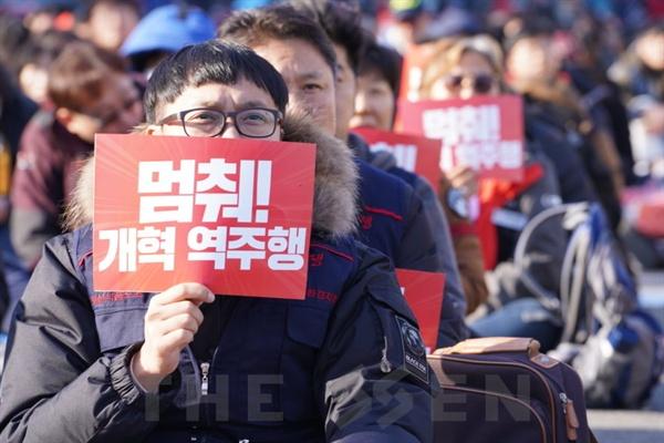 피켓든 참가자  1일 국회 앞에서 민중대회가 열린 가운데 한 참가자가 피켓을 들고 있다.