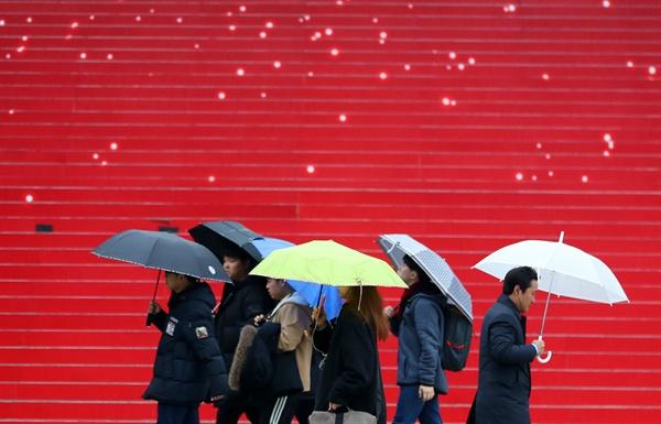 서울을 비롯한 중부지역에 겨울비가 내렸던 지난 3일 오전 서울 광화문 세종문화회관 계단 앞으로 시민들이 길을 지나고 있는 모습.