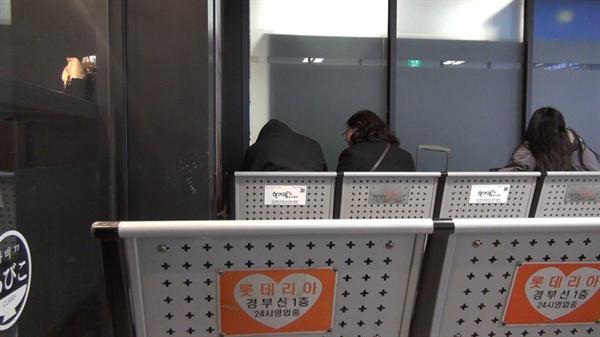 사람이 많은 고속터미널 대합실에서 휴식하는 여성홈리스와 아웃리치 상담원