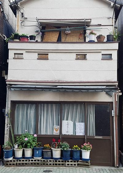 일본 주택가의 2층짜리 가정집 앞에 화분들이 놓여져있다.