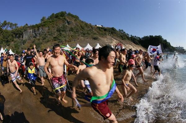 서귀포겨울바다 국제펭귄수영대회 서귀포겨울바다 국제펭귄수영대회에 참가한 관광객들이 바다로 뛰어들고 있다.