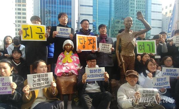 소녀상을 지키는 부산시민행동 등이 마련한 '한일 위안부 합의 무효와 강제징용노동자상 건립을 위한 공동행동'이 26일 오후 부산 일본영사관 인근에서 열렸다. 집회에 참가한 시민들이 일본영사관 앞 위안부 평화의 소녀상, 노동자상 모형과 함께 기념촬영을 하고 있다.